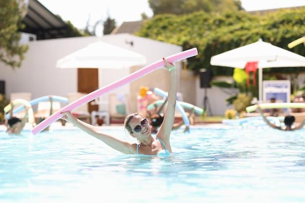 Mujer con gafas de sol de pie en la piscina y sosteniendo fideos para nadar aeróbicos acuáticos en vacaciones