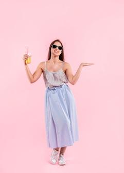 Mujer en gafas de sol de pie y sosteniendo el vaso de jugo