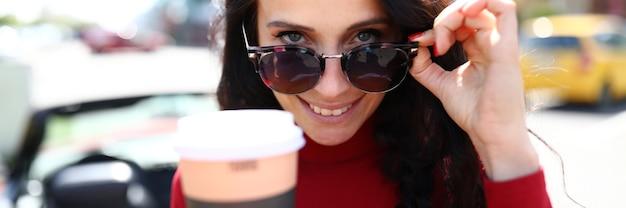 Mujer con gafas de sol tiene bebida caliente en sus manos