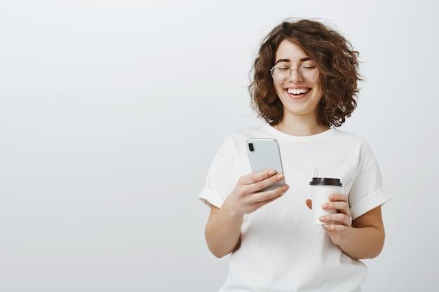 Mujer con gafas sonriendo al mensaje de texto del teléfono móvil, tomando café en el descanso de la oficina