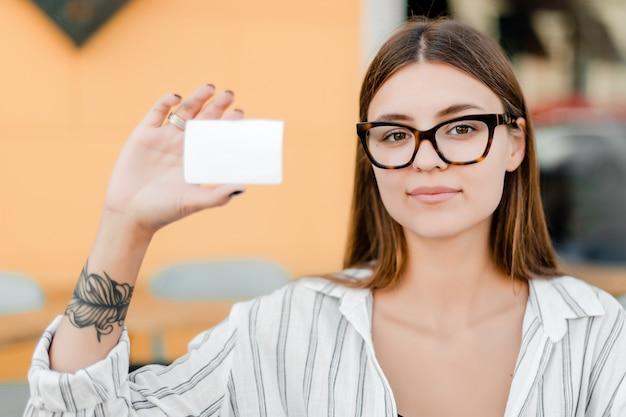 Mujer de gafas con tarjeta en blanco en la mano al aire libre
