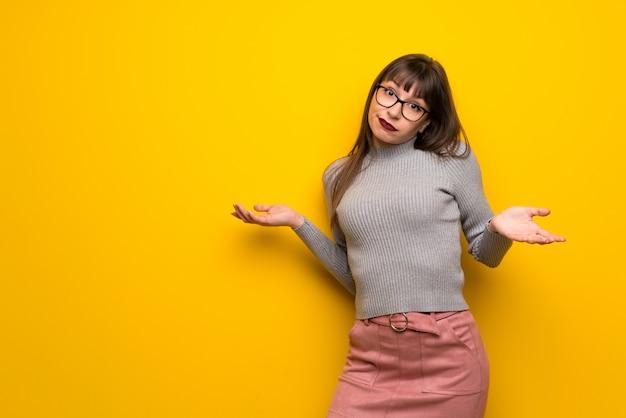Mujer con gafas teniendo dudas al levantar manos y hombros.