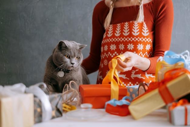 Mujer y gato en la mesa son cajas de embalaje con regalos de navidad