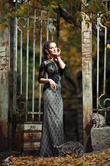 Mujer con gatos y una reja de hierro oxidada