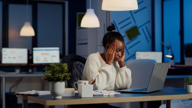 Mujer gerente africana con exceso de trabajo masajeando la cabeza mientras está sentado en el lugar de trabajo en la oficina de puesta en marcha trabajando horas extras en la computadora portátil. empresaria tensa agotada respetando el plazo de afrontamiento de la migraña