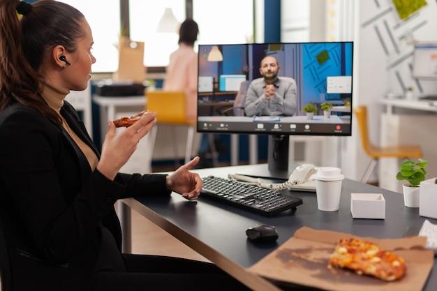 Mujer gerente discutiendo con el empresario remoto durante la videollamada en línea con almuerzo de entrega