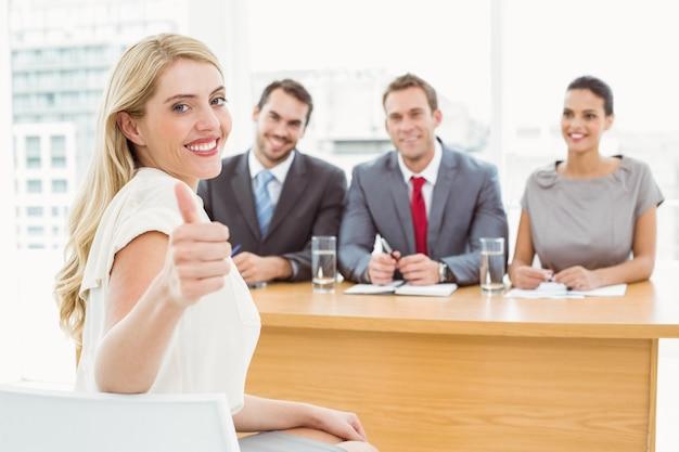 Mujer gesticulando pulgares arriba frente a funcionarios de personal corporativo