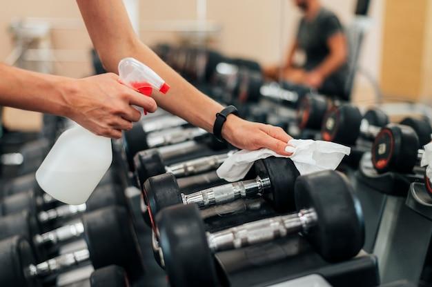 Mujer en el gimnasio desinfectando pesas antes de usarlas