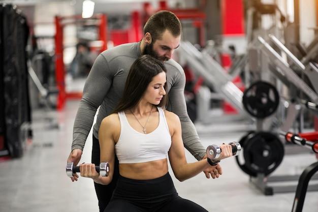 Mujer en el gimnasio con entrenador