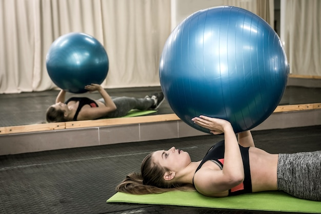 Mujer en el gimnasio haciendo ejercicios con bola grande