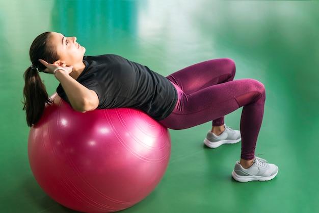 Mujer en el gimnasio haciendo ejercicios con pelota de pilates en la espalda