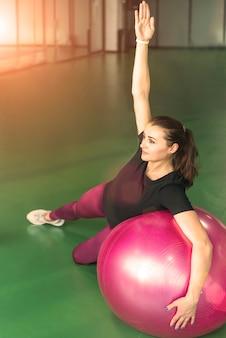Mujer en el gimnasio haciendo ejercicios con pelota de pilates con su mano levantarse