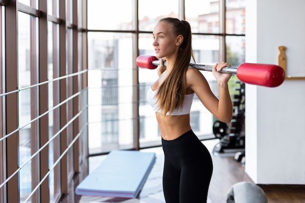 Mujer en el gimnasio levantando pesas bar