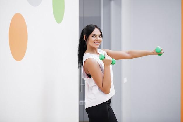 Mujer de gimnasio. mujer adolescente trabajando en el gimnasio con pesas