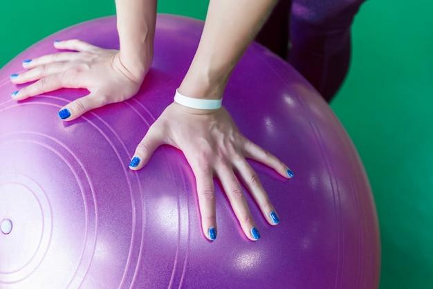 Mujer en el gimnasio con pelota de pilates, vista cercana