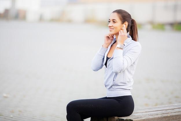Mujer de gimnasio. retrato de una hermosa joven fitness escuchar música