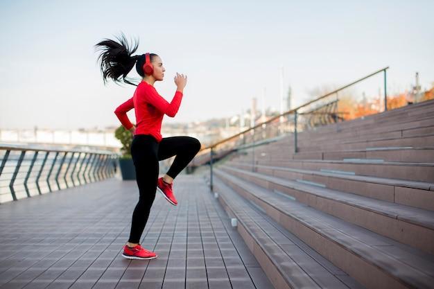 Mujer de gimnasio saltando al aire libre