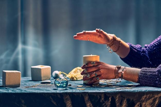 Mujer gitana bruja usando velas llama para hechizo mágico durante brujería mística