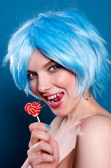 Mujer glamorosa alegre en peluca azul con una piruleta en sus manos