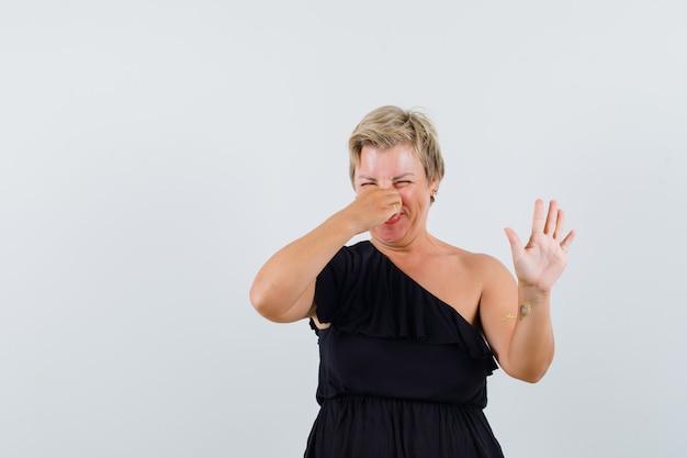 Mujer glamorosa en blusa negra pellizcando su nariz mientras levanta la mano de manera rechazada y se ve incómoda