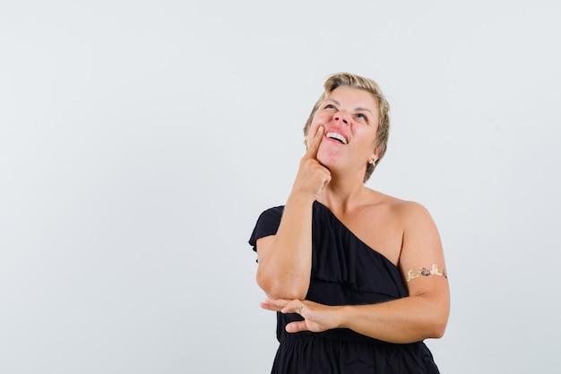 Mujer glamorosa en blusa negra que sufre de dolor de muelas y parece preocupada