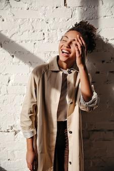 Mujer glamorosa en gabardina riendo con los ojos cerrados