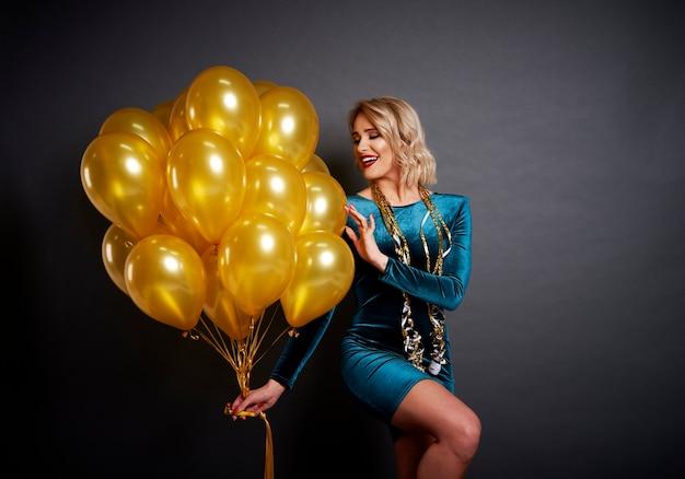 Mujer glamorosa con globos dorados sobre el negro