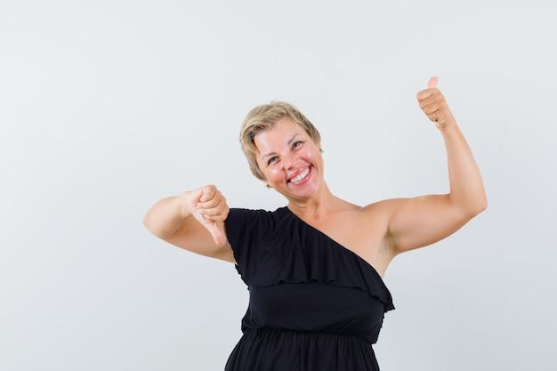 Mujer glamorosa mostrando el pulgar hacia arriba y hacia abajo en blusa negra y mirando vacilante. vista frontal.