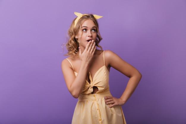 Mujer glamorosa pensativa con cinta amarilla mirando hacia arriba. retrato interior de modelo femenino de buen humor en lindo traje de verano.