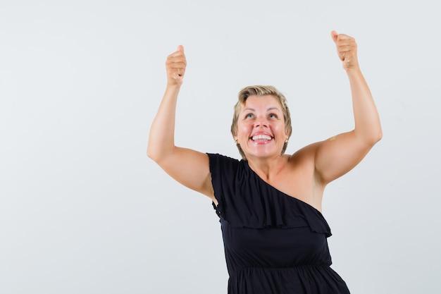 Mujer glamorosa posando como marco de elevación en vista frontal blusa negra.