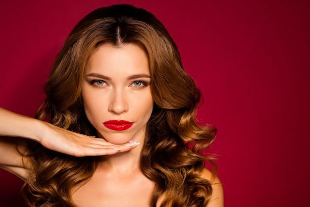 Mujer glamorosa posando contra la pared roja