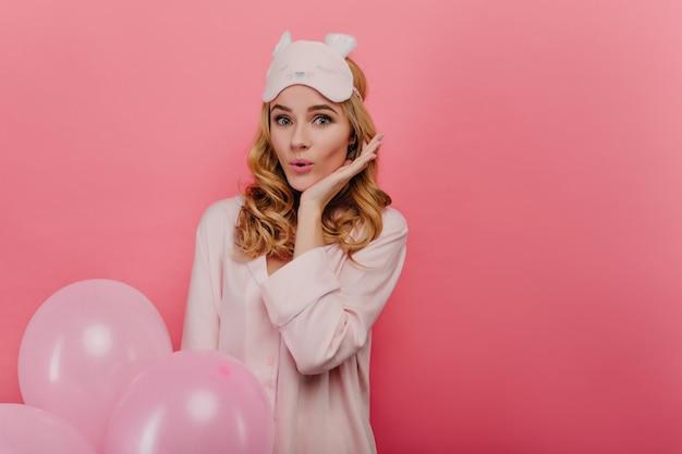 Mujer glamorosa sorprendida con peinado ondulado disfrutando de cumpleaños en la mañana. chica guapa con antifaz y pijama con globos rosados.