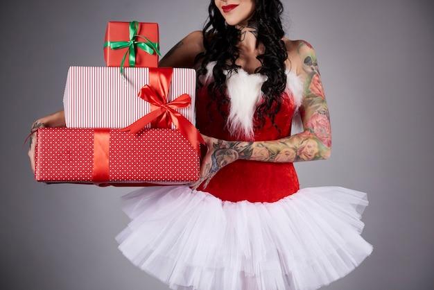 Mujer glamorosa sosteniendo una pila de regalo de navidad