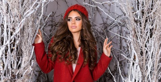 Mujer de glamour de belleza en el parque de invierno helado. hermosa mujer joven con sombrero de punto rojo, peinado ondulado increíble, labios carnosos y maquillaje brillante.