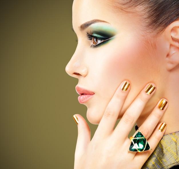 Mujer glamour con hermosas uñas doradas y anillo de esmeralda en las manos