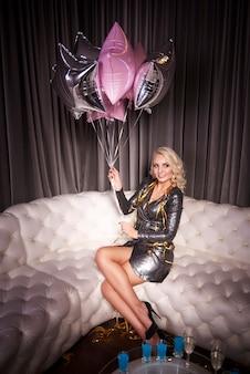 Mujer con globo sentado en el sofá en la fiesta de año nuevo