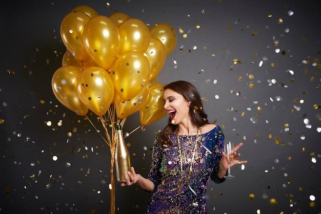 Mujer con globos y champagne entre confeti