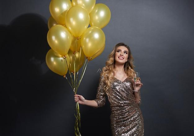 Mujer con globos y champán mirando hacia arriba