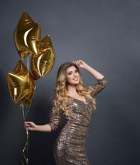 Mujer con globos en forma de estrella bailando