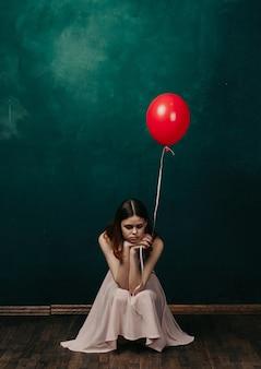 Mujer con globos en sus manos con un vestido