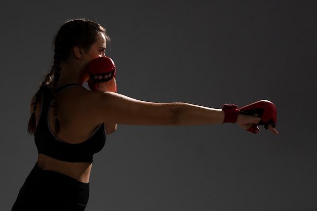 Mujer golpeando con guantes de box