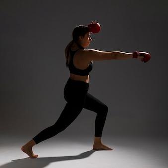 Mujer golpeando de lado con guantes de box