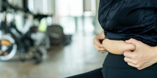 Mujer gorda asiática agarrando su vientre de estómago