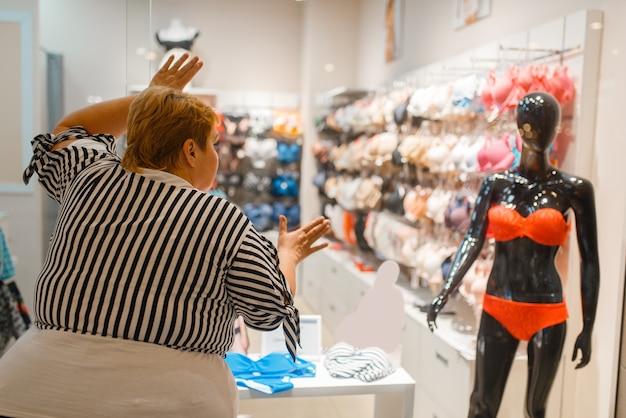Mujer gorda cerca de la vitrina con ropa interior para cuerpo delgado. persona de sexo femenino con sobrepeso soñando en la tienda con lencería, problema de obesidad