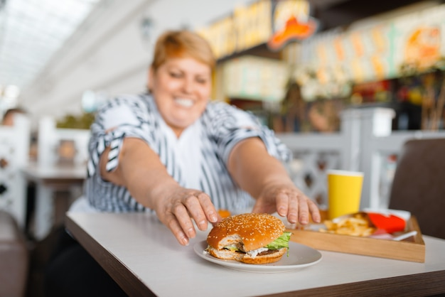 Mujer gorda comiendo alimentos ricos en calorías en el centro comercial