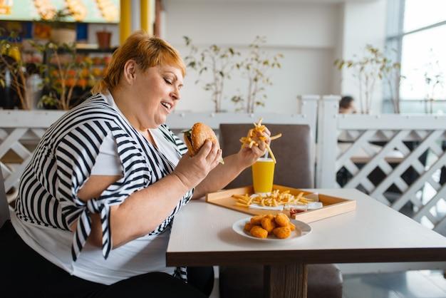 Mujer gorda comiendo alimentos ricos en calorías en el restaurante