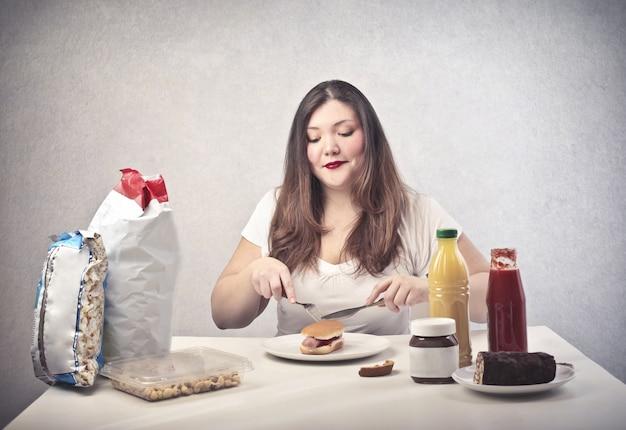 Mujer gorda comiendo una hamburguesa
