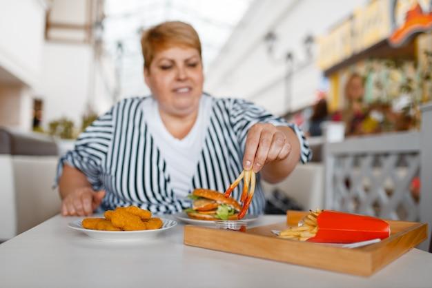 Mujer gorda comiendo papas fritas en el patio de comidas del centro comercial. persona de sexo femenino con sobrepeso en la mesa con comida chatarra, problema de obesidad