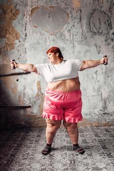 Mujer gorda en entrenamiento con pesas, obesidad