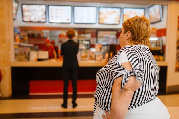Mujer gorda en el menú del restaurante de comida rápida. persona de sexo femenino con sobrepeso comprando comida rápida, problema de obesidad